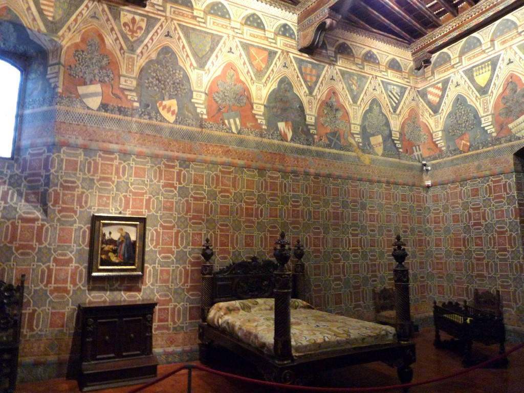 Bedroom with bed, crib, chairs, cassone, and devotional paintings