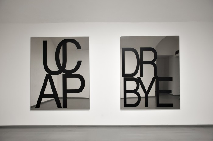 Be Andre, R BYE (don't believe everthing you read), 2014, vinyl lettering on polished stainless steel, 180 x 145 cm & UCAP, 2014, stainless steel, 180 cm x 145 cm.