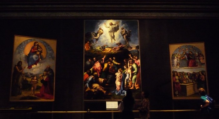 Raphael altarpieces in a darkened room in the Vatican Museums