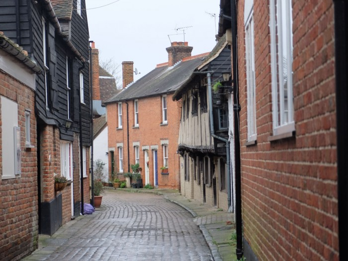 A curved dead end street with a 16th-century home whose windows were built to let in light for weavers