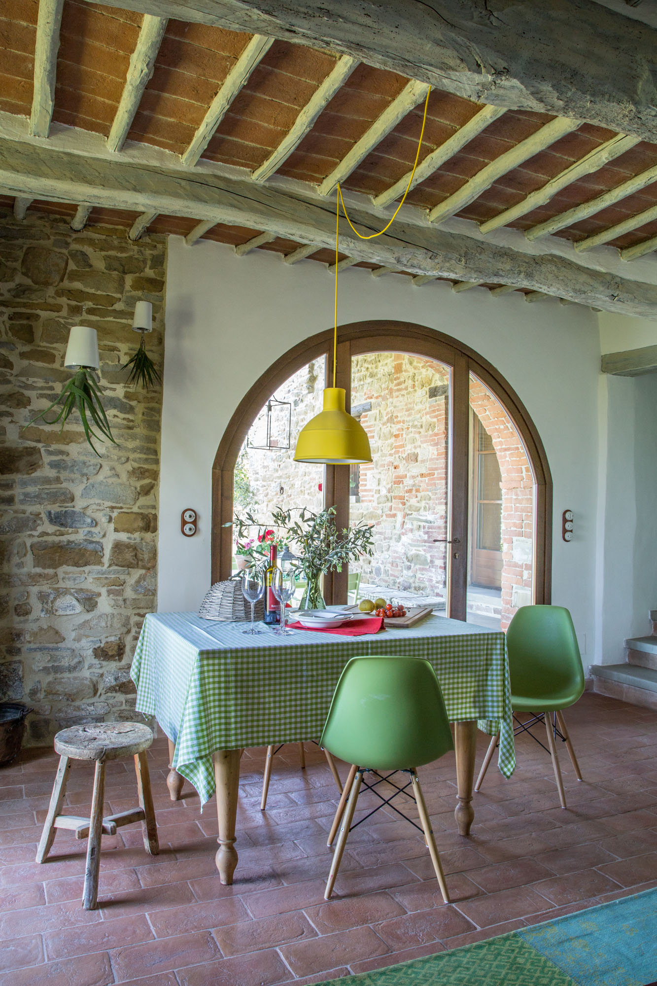 This country kitchen has all the standard elements of terracotta floors, beams and stone walls - made lighthearted with modern chairs and a simpatico checkered cloth!