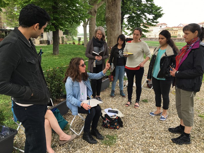 Students gather around Christine during a drawing lesson