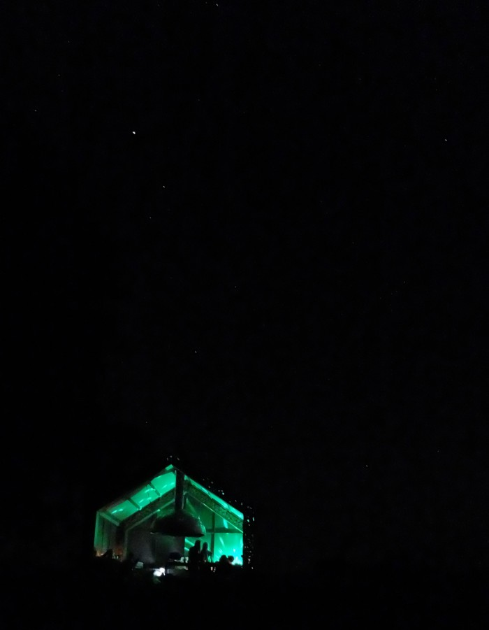 The fire hut lit up at night, and the stars above