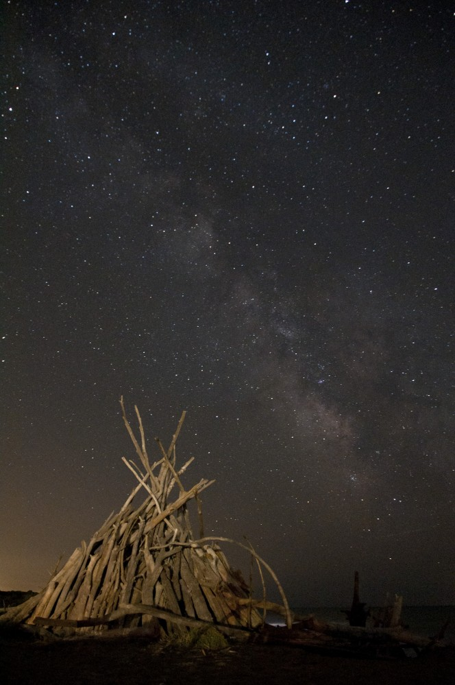 The Milky Way above a driftwood hut on the beach